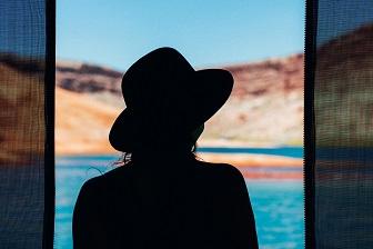 Fotografija žene sa šeširom koja gleda u daljinu.
